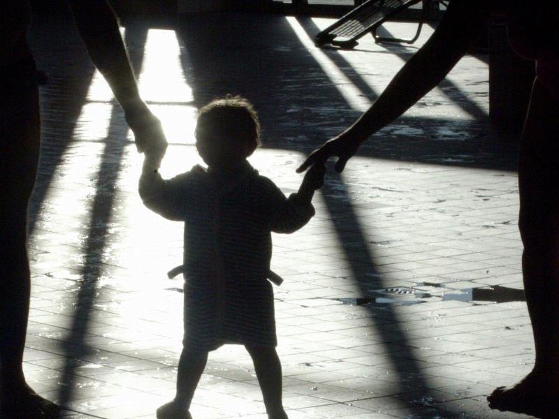 Bild zu Zwei Erwachsene halten ein Kind