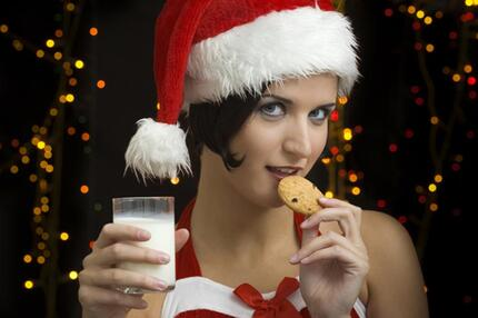 Frau im Weihnachtskostüm isst Keks