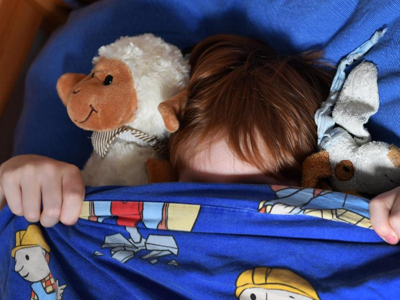 Bild zu Kind liegt unter der Bettdecke