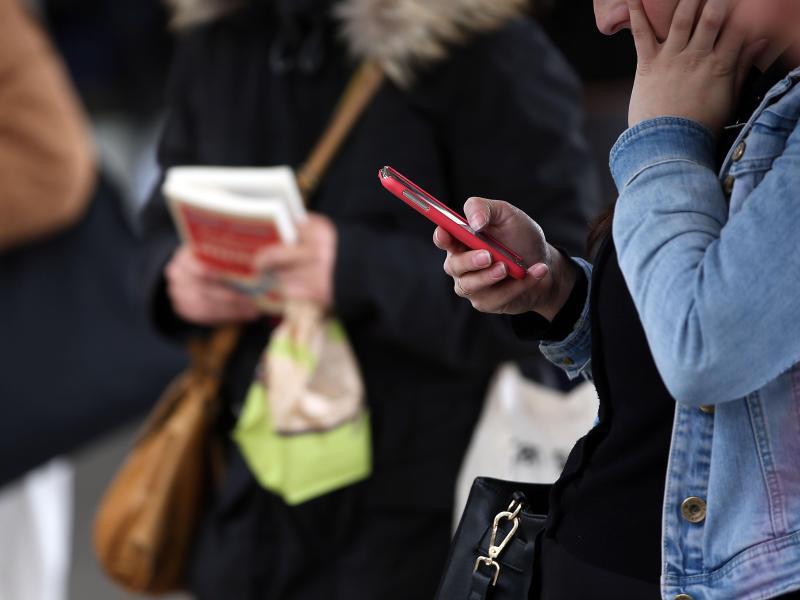 Bild zu Eine Frau blickt auf ihr Smartphone