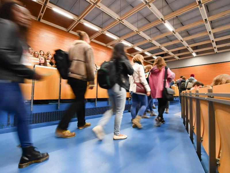 Bild zu Studierende kommen in einen Hörsaal