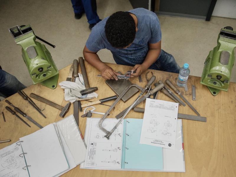 Bild zu Flüchtling arbeitet an Werkbank