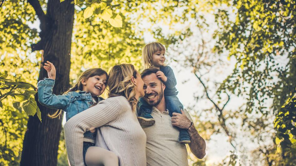 Eltern mit ihren zwei Kindern sind im Wald
