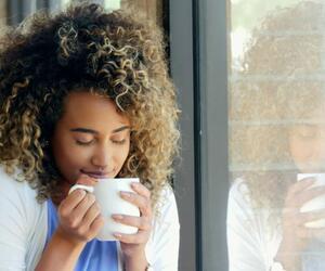 Eine Frau trinkt heißen Ingwertee um ihre Halsschmerzen zu lindern.